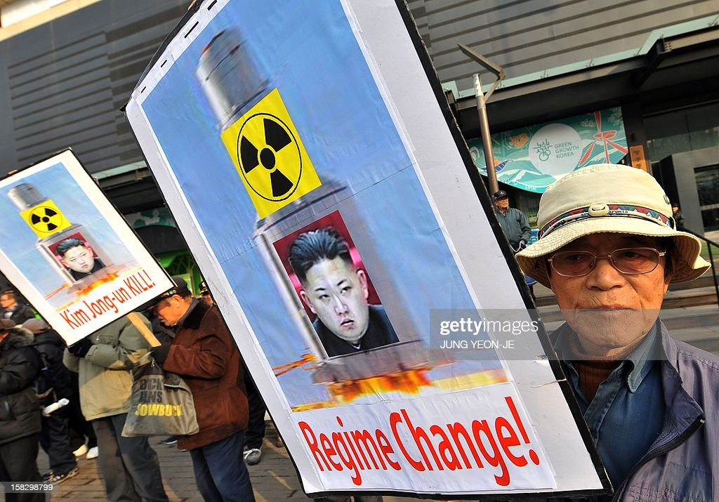 South Korean conservative activists hold placards showing a portrait of North Korean leader Kim Jong-Un during a protest denouncing North Korea's rocket launch, in Seoul on December 13, 2012. North Korea's rocket launch is a timely boost for its young leader, securing his year-old grip on power and laying to rest the humiliation of a much-hyped but failed launch eight months ago, analysts say.