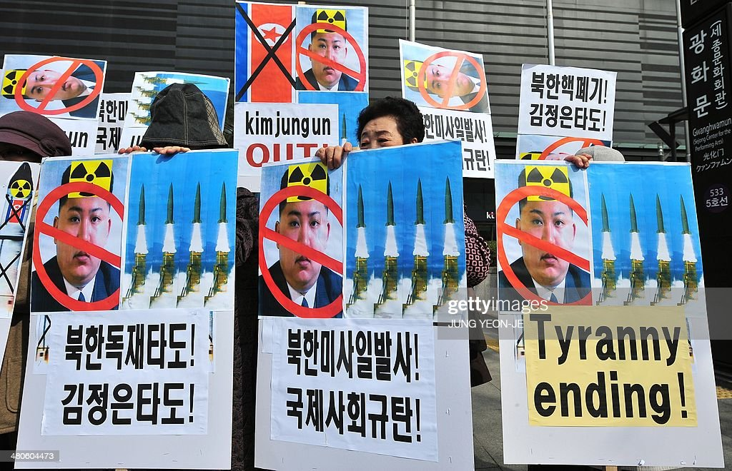 South Korean conservative activists hold placards showing portrait of North Korean leader Kim Jong-Un during a rally denouncing North Korea's missile test-launch in Seoul on March 26, 2014. North Korea test-fired two medium-range ballistic missiles on March 26, prompting a stern US reaction after President Barack Obama hosted a landmark Japan-South Korea summit aimed at uniting the three nations against Pyongyang's nuclear threat.