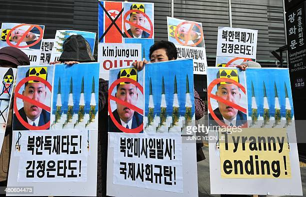 South Korean conservative activists hold placards showing portrait of North Korean leader Kim JongUn during a rally denouncing North Korea's missile...