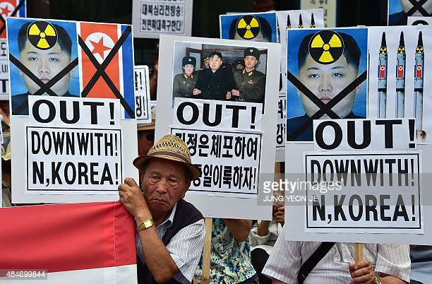 South Korean conservative activists hold placards showing portraits of North Korean leader Kim JongUn during a rally denouncing North Korea's rocket...
