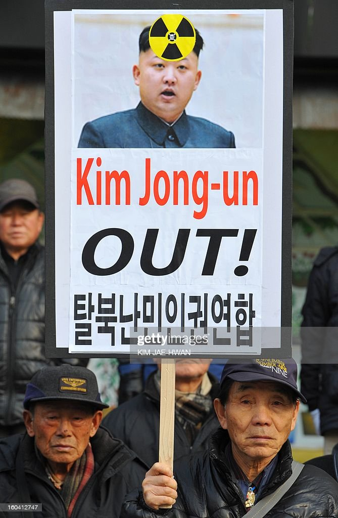 South Korean conservative activists hold up a placard displaying a picture of North Korean leader Kim Jong-Un during an anti-Pyongyang rally urging North Korea to abandon nuclear weapons in Seoul on January 31. South Korean President Lee Myung-Bak held an emergency security meeting on Jaunary 31 that warned North Korea of 'serious consequences' if it went through with an expected nuclear test.