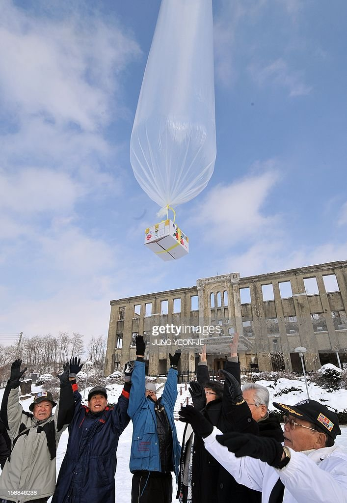 South Korean conservative activists release a balloon carrying anti-North Korea leaflets in front of former North Korean Labor Party Cheorwon Office Building in the South Korean border county of Cheorwon on January 1, 2013. About 30 activists released seven balloons carrying 28,000 leaflets shouting 'Down with North Korea's dynastic dictorship!'. AFP PHOTO / JUNG YEON-JE