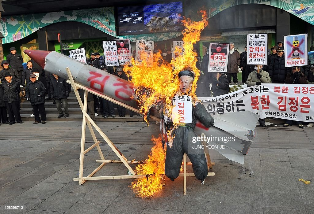 South Korean conservative activists set fire to a mock North Korean missile and an effigy (C) of North Korean leader Kim Jong-Un during a protest denouncing North Korea's rocket launch the day before, in Seoul on December 13, 2012. North Korea's rocket launch is a timely boost for its young leader, securing his year-old grip on power and laying to rest the humiliation of a much-hyped but failed launch eight months ago, analysts say. AFP PHOTO / JUNG YEON-JE