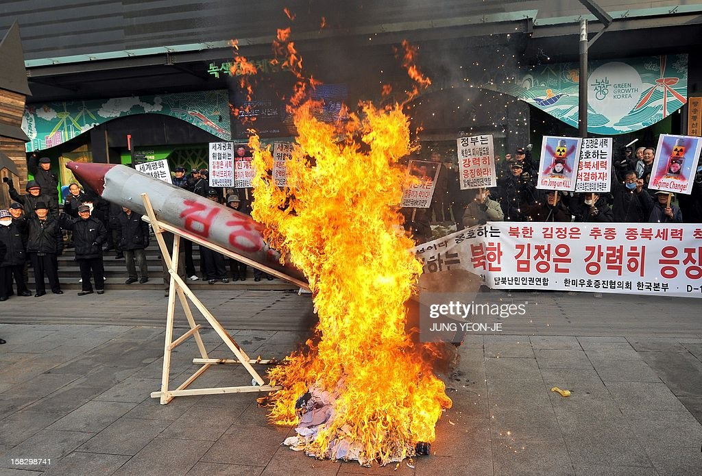 South Korean conservative activists set fire to a mock North Korean missile and an effigy (C, unseen) of North Korean leader Kim Jong-Un during a protest denouncing North Korea's rocket launch the day before, in Seoul on December 13, 2012. North Korea's rocket launch is a timely boost for its young leader, securing his year-old grip on power and laying to rest the humiliation of a much-hyped but failed launch eight months ago, analysts say. AFP PHOTO / JUNG YEON-JE