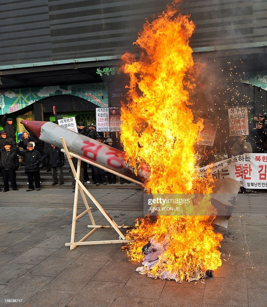 South Korean conservative activists set fire to a mock North Korean missile and an effigy (C, unseen) of North Korean leader Kim Jong-Un during a protest denouncing North Korea's rocket launch the day before, in Seoul on December 13, 2012. North Korea's rocket launch is a timely boost for its young leader, securing his year-old grip on power and laying to rest the humiliation of a much-hyped but failed launch eight months ago, analysts say.