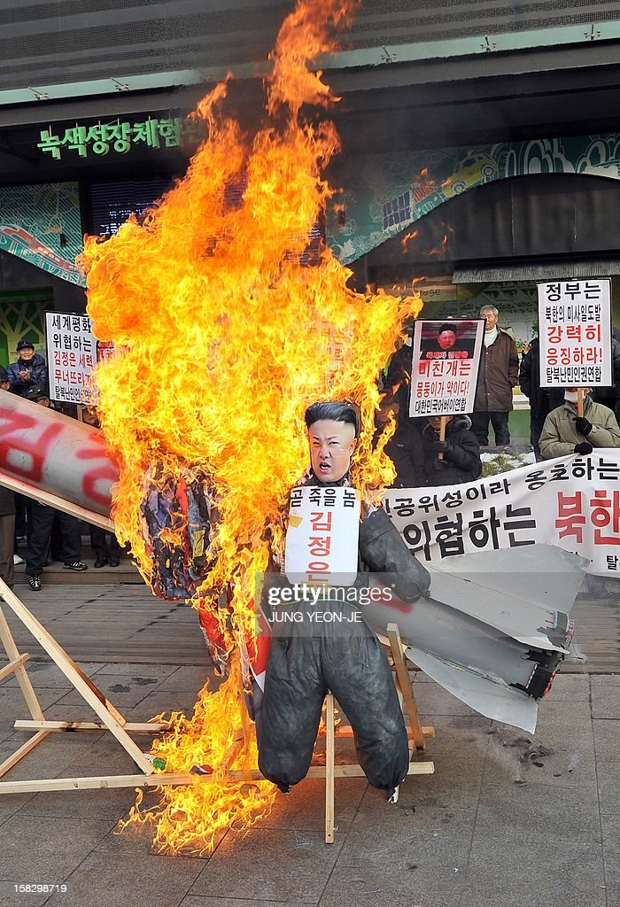 South Korean conservative activists set fire to an effigy (C) of North Korean leader Kim Jong-Un next to a mock North Korean missile (behind) during a protest denouncing North Korea's rocket launch...