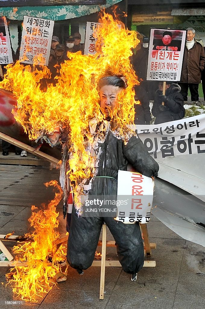 South Korean conservative activists set fire to an effigy (C) of North Korean leader Kim Jong-Un next to a mock North Korean missile (behind) during a protest denouncing North Korea's rocket launch the day before, in Seoul on December 13, 2012. North Korea's rocket launch is a timely boost for its young leader, securing his year-old grip on power and laying to rest the humiliation of a much-hyped but failed launch eight months ago, analysts say. AFP PHOTO / JUNG YEON-JE