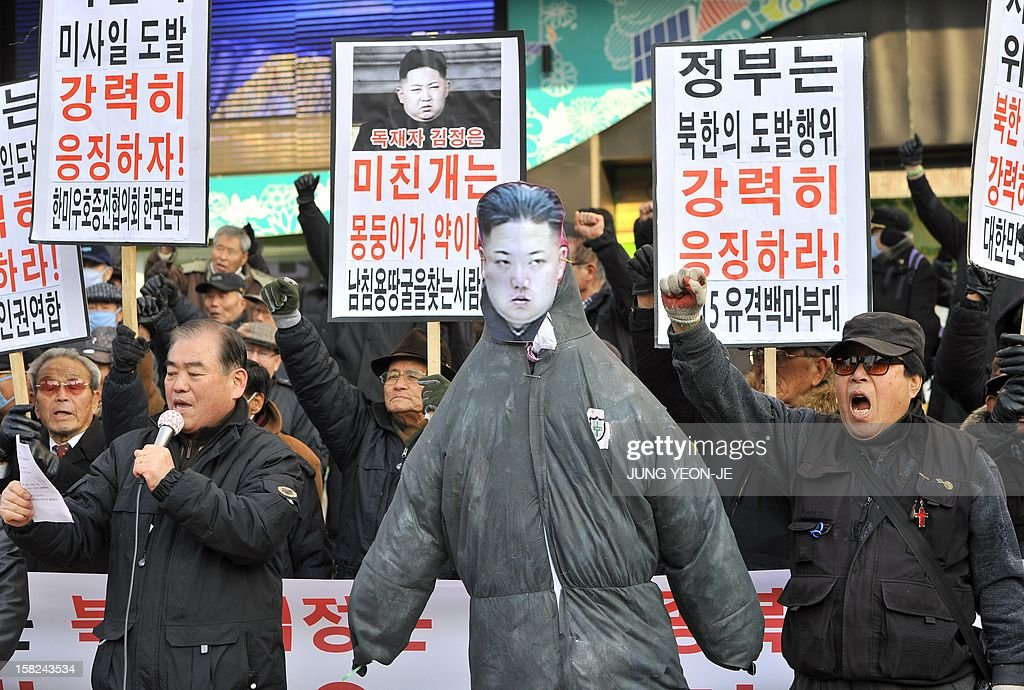 South Korean conservative activists shout slogans beside an effigy (C) of North Korean leader Kim Jong-Un during a protest denouncing North Korea's rocket launch, in Seoul on December 12, 2012. North Korea's rocket launch is evidence of a new ballistic missile capability that sharply raises the stakes over Pyongyang's nuclear programme and poses a direct threat to the United States, analysts say. AFP PHOTO / JUNG YEON-JE