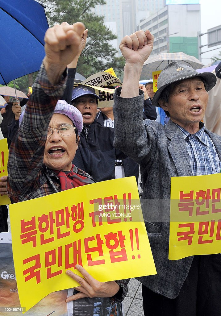 South Korean conservative activists shout slogans during an anti-North Korea rally in Seoul on May 25, 2010 after South Korea announced reprisals against North Korea for the sinking of a warship. North Korea's military accused the South Korean navy of trespassing in its waters and threatened military action in response. The yellow paper reads 'Condemn North Korea's barbaric act!! Grand national unity!!'