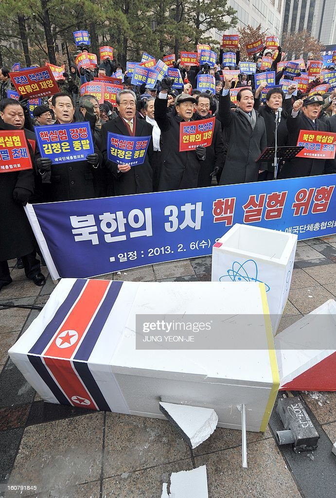 South Korean conservative activists shout slogans in front of a broken mock North Korean nuclear missile during a protest against North Korea's threat of its nuclear test, in Seoul on February 6, 2013. North Korea warned on February 5, of making a move 'beyond imagination,' as the communist state ramps up daily threats of an apparently imminent nuclear test. The banner reads 'A rally denouncing the threat of the 3rd nuclear test by North Korea'.