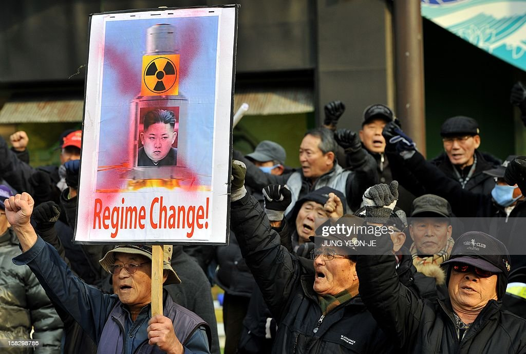 South Korean conservative activists shout slogans with a placard showing a portrait of North Korean leader Kim Jong-Un during a protest denouncing North Korea's rocket launch the day before, in Seoul on December 13, 2012. North Korea's rocket launch is a timely boost for its young leader, securing his year-old grip on power and laying to rest the humiliation of a much-hyped but failed launch eight months ago, analysts say. AFP PHOTO / JUNG YEON-JE