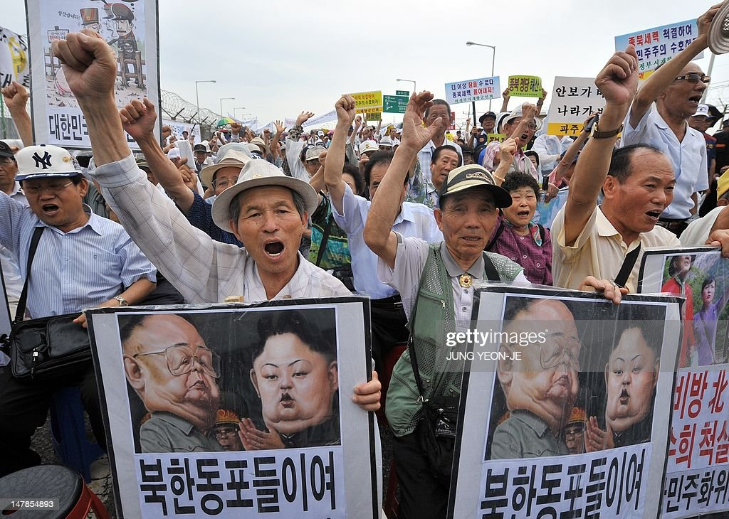 South Korean conservative activists shout slogans with placards showing a caricature of North Korea's current leader Kim Jong-Un (R) and his father Kim Jong-Il (L) during an anti-Pyongyang rally in Paju near a border bridge leading to Panmunjom, on July 5, 2012. A left-wing South Korean activist was detained when he returned home from an illegal trip to North Korea and a meeting with its ceremonial head of state, police said.