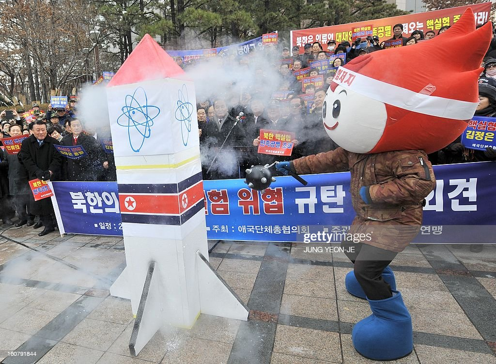 A South Korean conservative activists smashes a mock North Korean nuclear missile during a protest against North Korea's threat of its nuclear test, in Seoul on February 6, 2013. North Korea warned on February 5 of making a move 'beyond imagination,' as the communist state ramps up daily threats of an apparently imminent nuclear test. The banner reads 'A rally denouncing the threat of the 3rd nuclear test by North Korea'. AFP PHOTO / JUNG YEON-JE