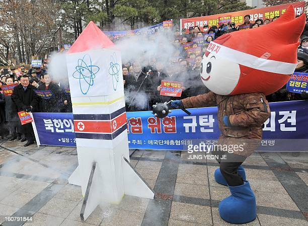 A South Korean conservative activists smashes a mock North Korean nuclear missile during a protest against North Korea's threat of its nuclear test...