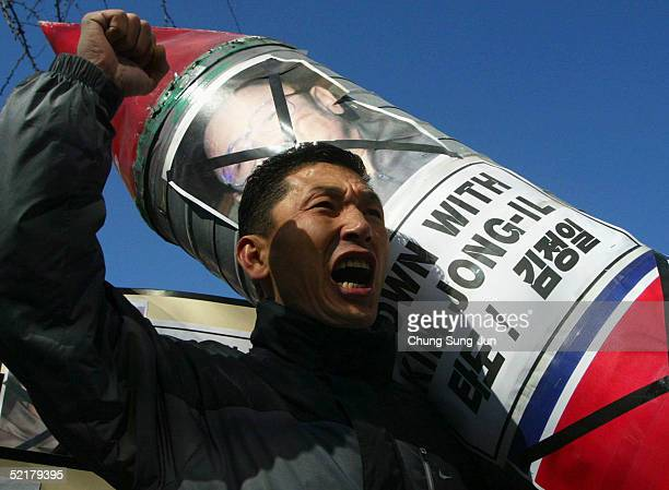 South Korean conservative protester carries a model of a nuclear missile displaying a portrait of North Korean leader Kim JongIl during antiNorth...