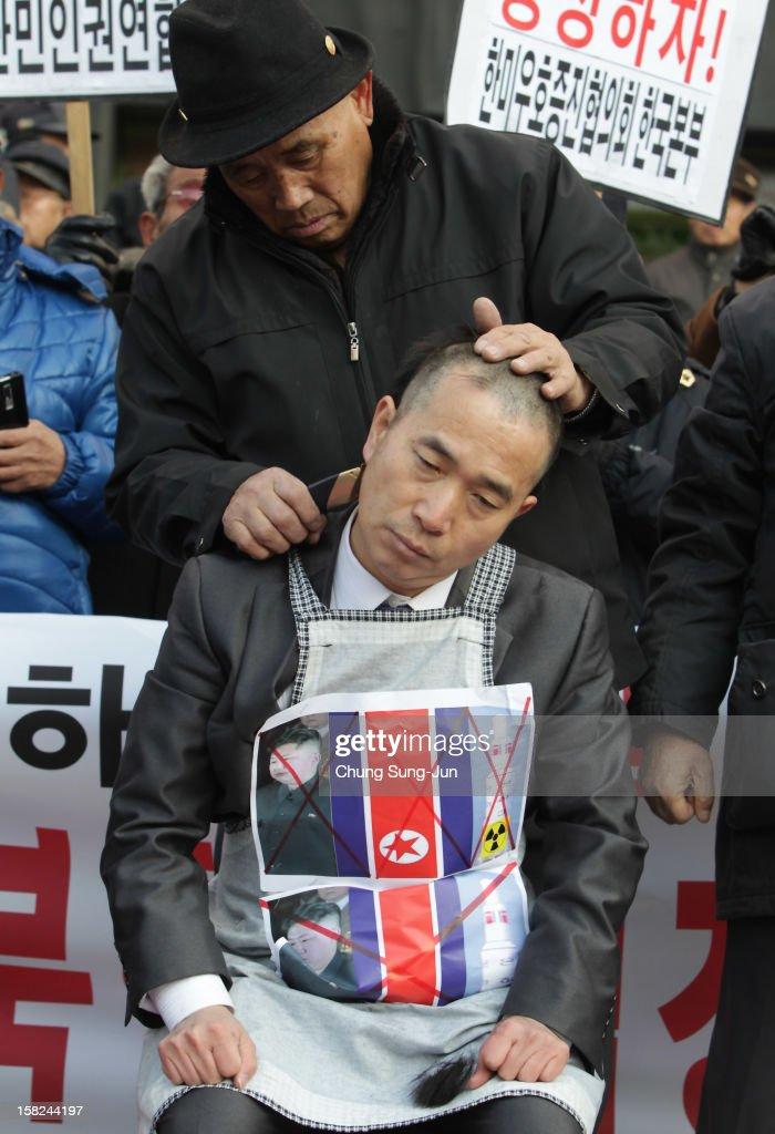 A South Korean conservative protester sits as his head is shaved during an anti-North Korea rally reacting to North Korea having launched a long-range missile on December 12, 2012 in Seoul, South Korea. North Korea launched a long range missile on 9:49am local time.