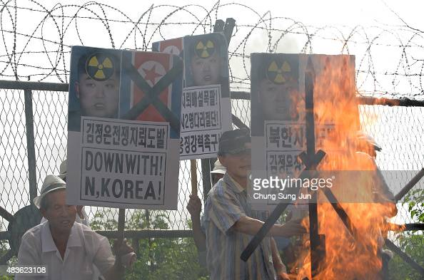 South Korean conservative protesters burn a effigy of North Korea leader Kim JongUn and placards during a antiNorth Korea rally in front of barbed...