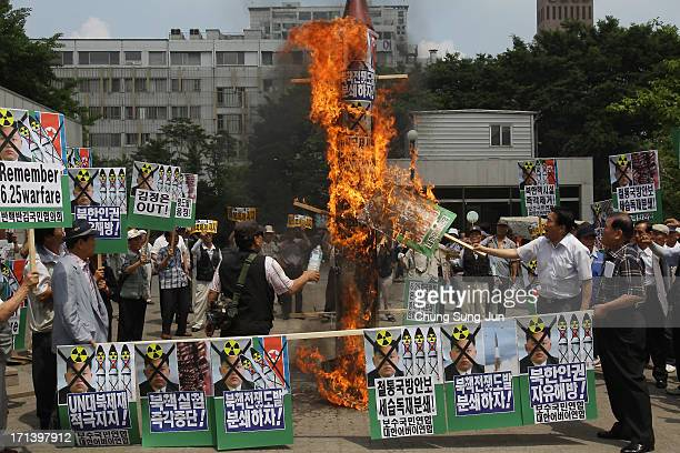 South Korean conservative protesters burn a mock of North Korea's missile and antiNorth Korea placards during an antiNorth Korea rally to mark 63rd...