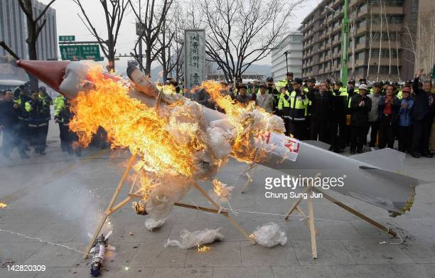 South Korean conservative protesters burn a mockup of a North Korean missile during an antiNorth Korea rally protesting against North Korea launching...