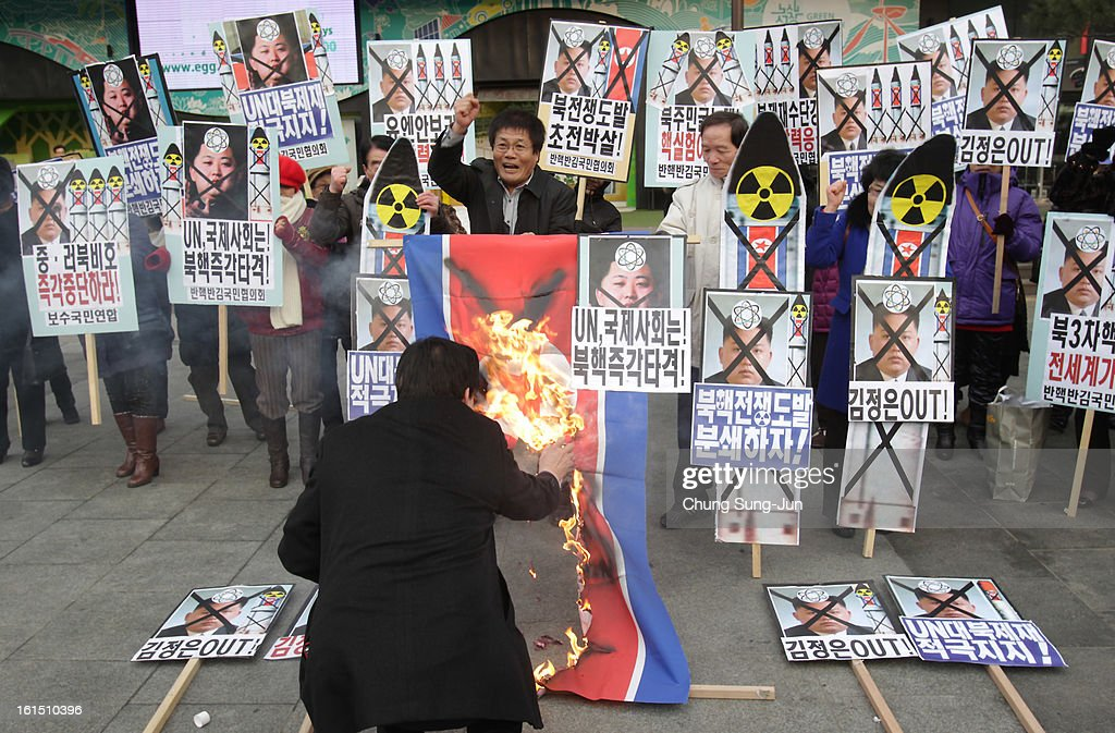 South Korean conservative protesters burn a North Korean flag during an anti-North Korea rally demonstrating against North Korea's nuclear test on February 12, 2013 in Seoul, South Korea. North Korea confirmed it had successfully carried out an underground nuclear test, as a shallow earthquake with a magnitude of 4.9 was detected by several international monitoring agencies. South Korea and Japan both assembled an emergency meeting of their respective national security teams after the incident.