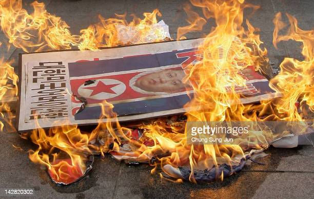 South Korean conservative protesters burn a portrait of North Korea's new leader Kim JongUn and a North Korean flag during an antiNorth Korea rally...