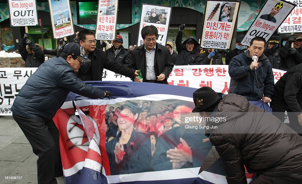 South Korean conservative protesters deface a North Korean flag during a rally demonstrating against North Koreas nuclear test on February 12, 2013 in Seoul, South Korea. North Korea confirmed it had successfully carried out an underground nuclear test as a shallow earthquake with a magnitude of 4.9 was detected by several international monitoring agencies. South Korea and Japan both assembled an emergency meeting of their respective national security teams after the incident.