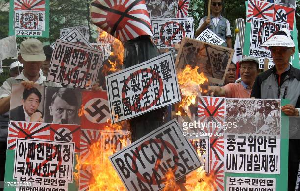 South Korean conservative protesters display antiJapan placards and burn an effigy of Japanese Prime Minister Shinzo Abe during a protest as South...