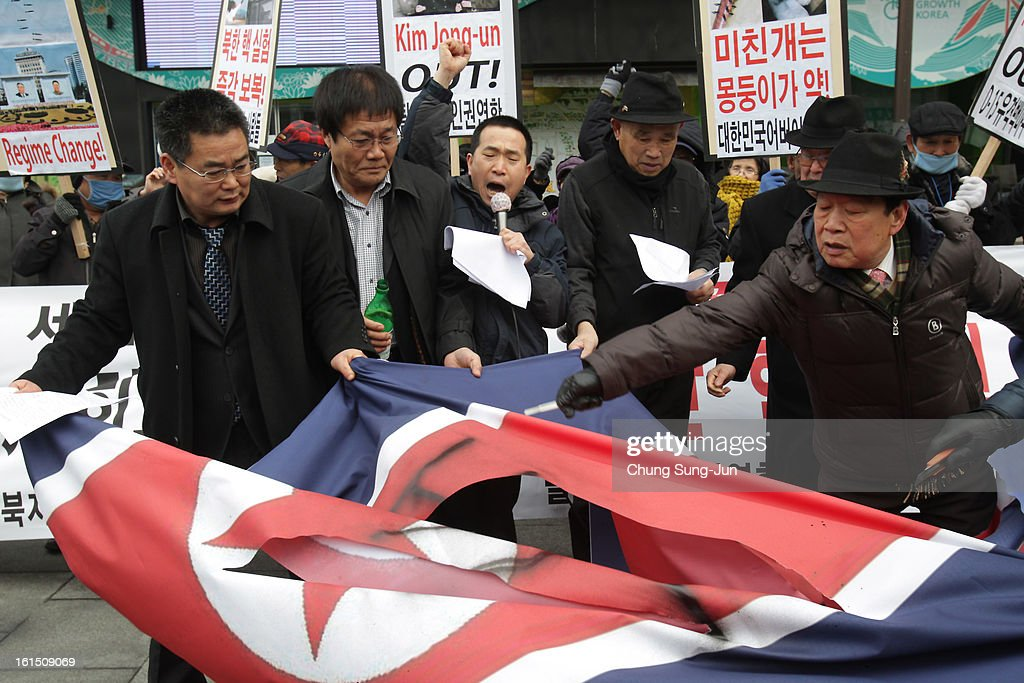 South Korean conservative protesters tear a North Korean flag during a rally demonstrating against North Koreas nuclear test on February 12, 2013 in Seoul, South Korea. North Korea confirmed it had successfully carried out an underground nuclear test as a shallow earthquake with a magnitude of 4.9 was detected by several international monitoring agencies. South Korea and Japan both assembled an emergency meeting of their respective national security teams after the incident.