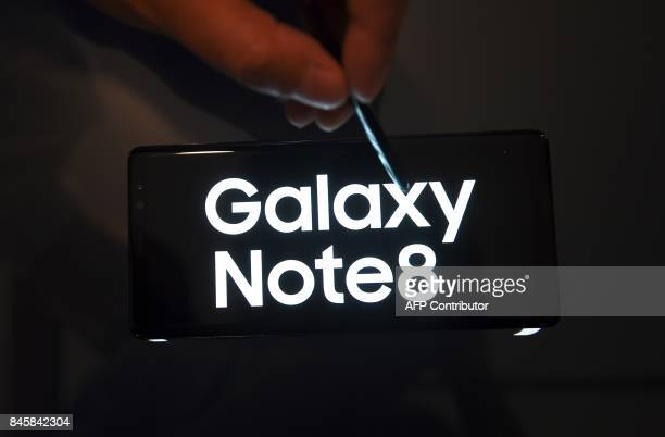 A South Korean employee demonstrates the Samsung Galaxy Note8 during a showcase to mark the domestic launch of Samsung Electronics' latest flagship...