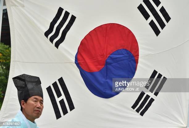 A South Korean family member of the war dead wears a traditional costume as he stands in front of the national flag during a memorial service to mark...