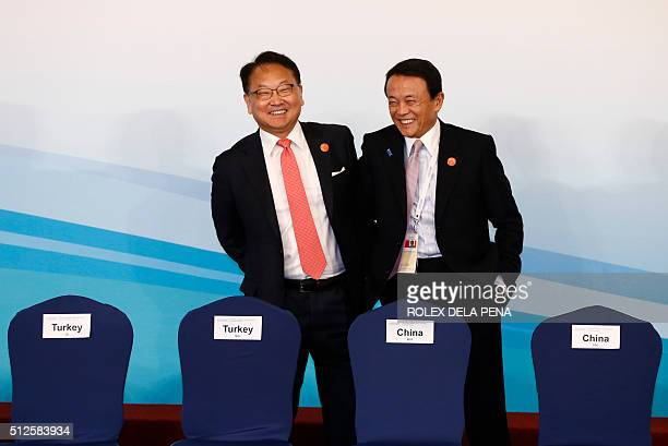 South Korean Finance Minister Yoo Ilho smiles with Japanese Finance Minister Taro Aso as they take their positions for a 'family photo' at the G20...