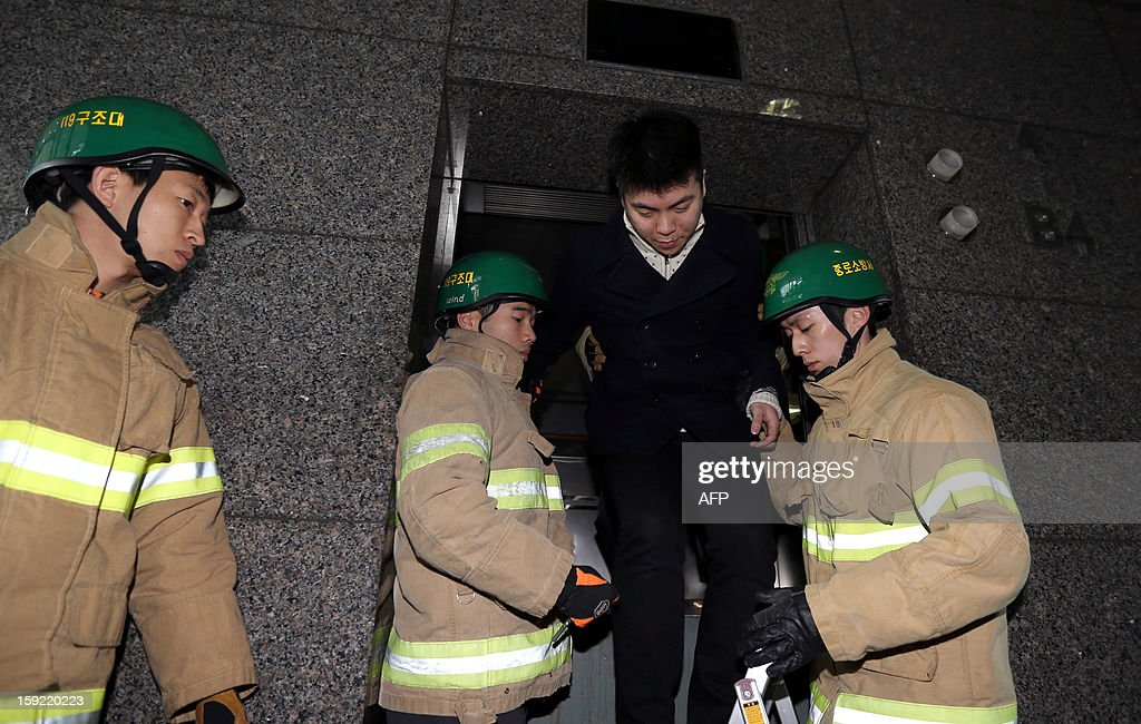 South Korean firefighters 'rescue' a man from an elevator during a national drill in the case of an emergency power blackout in Seoul on January 10, 2013. Sirens sounded across South Korea and subway systems grounded to a halt as the government held a national drill aimed at averting a countrywide power blackout. REPUBLIC OF KOREA OUT AFP PHOTO/DONG-A ILBO