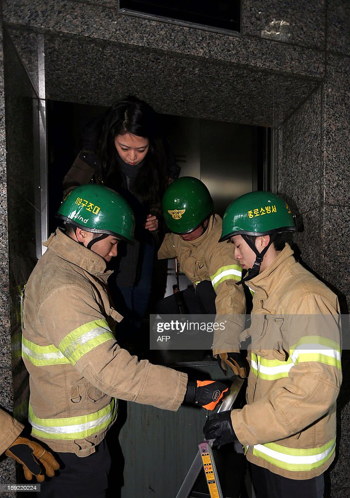 South Korean firefighters 'rescue' a woman (top) from an elevator during a national drill in the case of an emergency power blackout in Seoul on January 10, 2013. Sirens sounded across South Korea and subway systems grounded to a halt as the government held a national drill aimed at averting a countrywide power blackout. REPUBLIC
