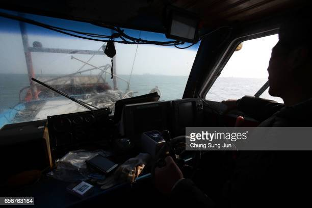 South Korean fisher drives a boat to the site of attempts to salvage sunken Sewol ferry in waters off Jindo on March 23 2017 in Jindogun South Korea...