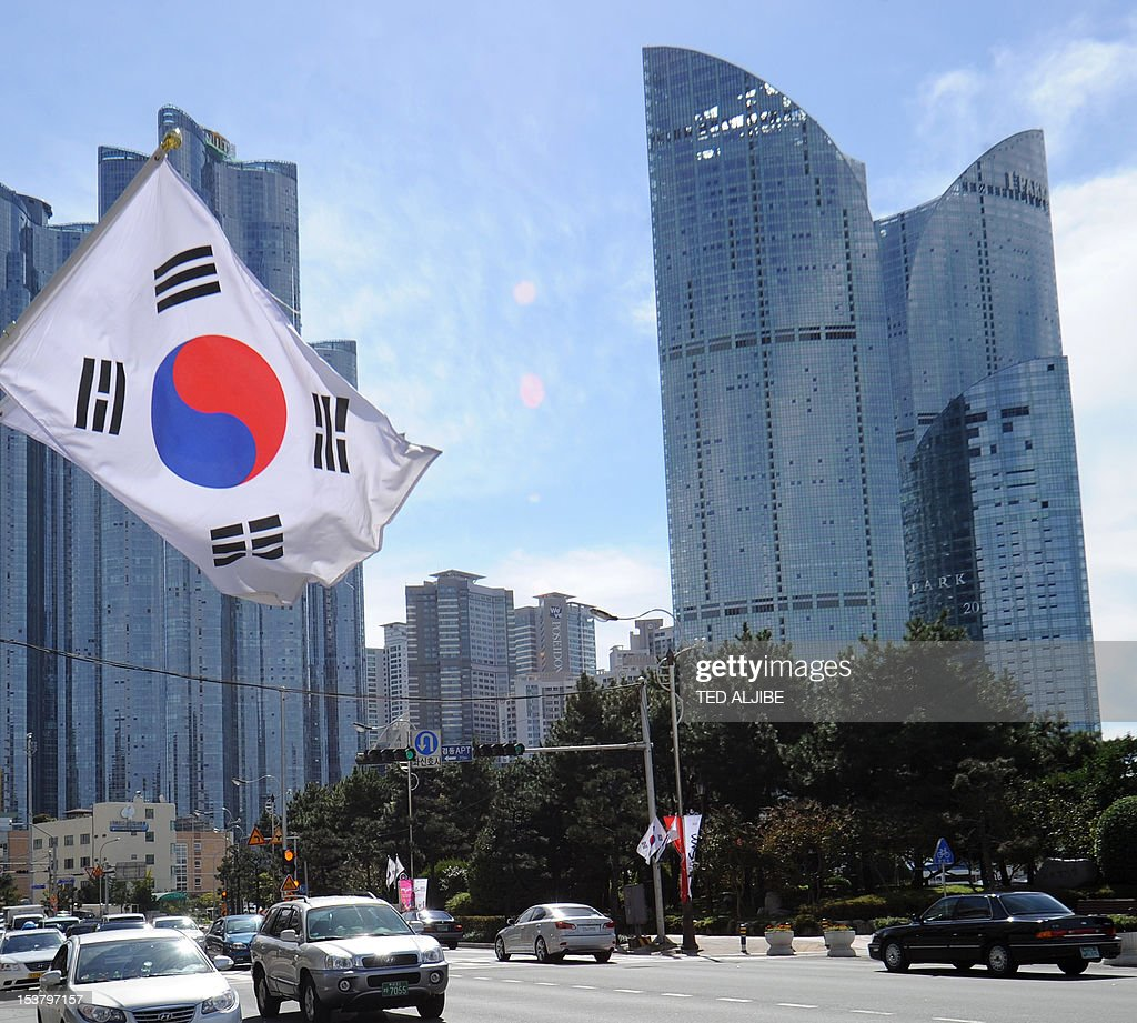 A South Korean flag (L) flutters in the wind as motorists drive on a road in front of a group of high rise commercial and residential buildings in downtown Busan, on October 9, 2012. South Korea announced steps to bolster its sagging property market, including easing restrictions imposed on some districts of the capital.