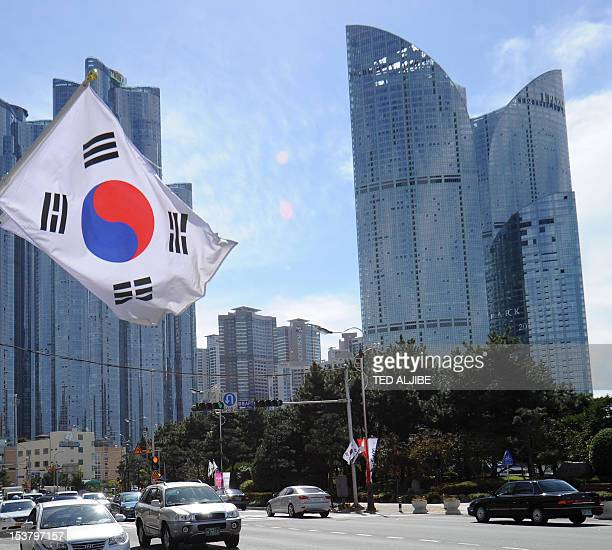 A South Korean flag flutters in the wind as motorists drive on a road in front of a group of high rise commercial and residential buildings in...