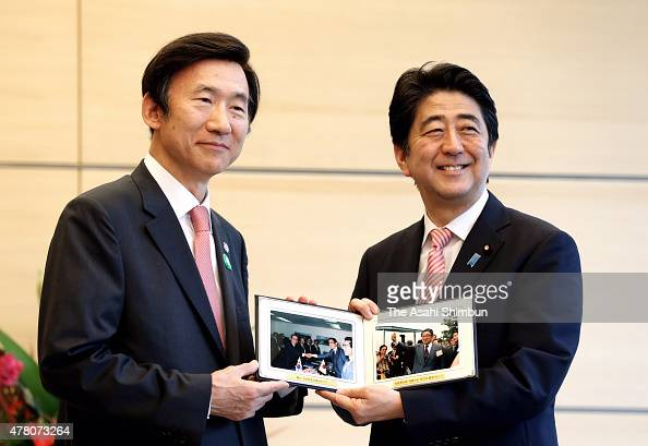 South Korean Foreign Minister Yun Byungse and Japanese Prime Minister Shinzo Abe pose with pictures of Abe's father and former Foreign Minister...