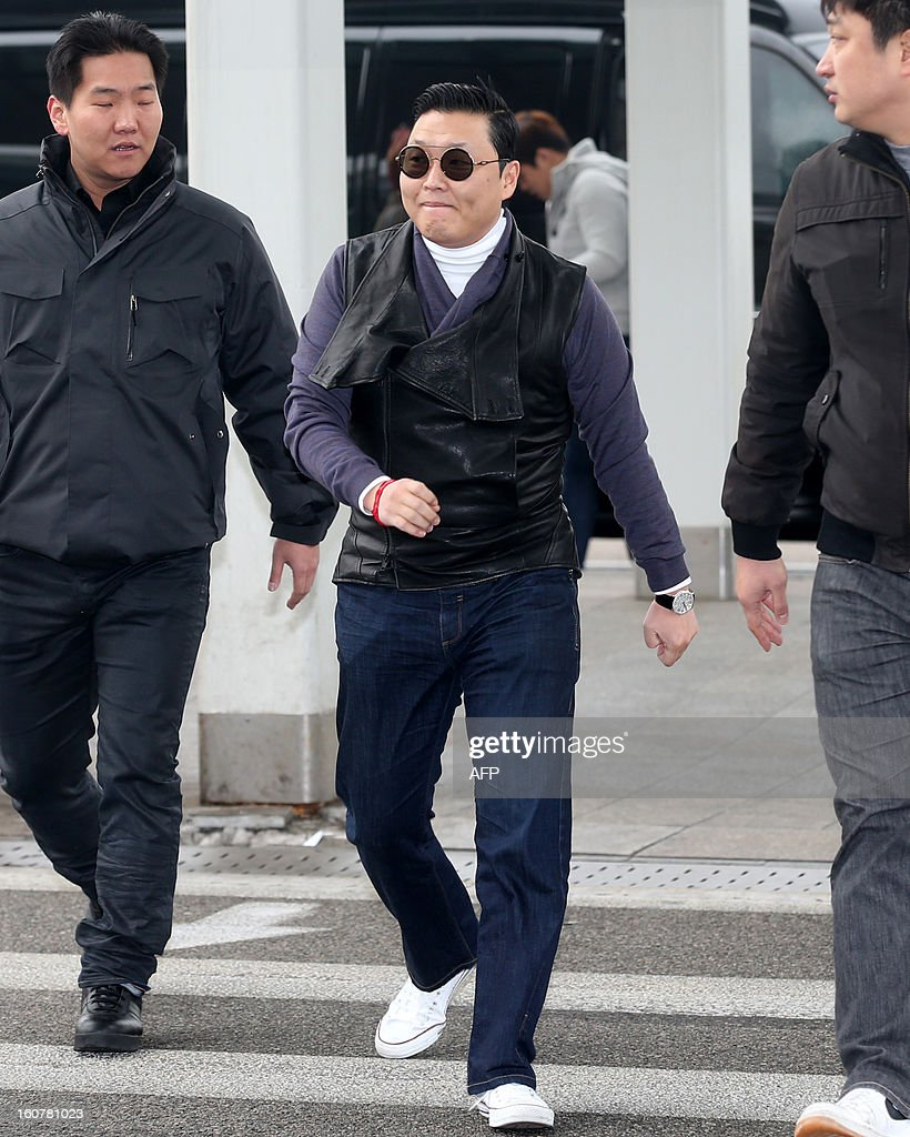 South Korean 'Gangnam Style' star Psy (C) is pictured at Incheon International Airport before his departure on a flight to Los Angeles after taking a one-day-rest in Seoul on February 5, 2013. REPUBLIC OF KOREA OUT JAPAN OUT AFP PHOTO/STARNEWS