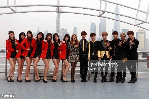 South Korean girl group Rainbow singer Park Gyuri and boy band AJAX pose on board a sightseeing ship on the Huangpu River on December 25 2013 in...
