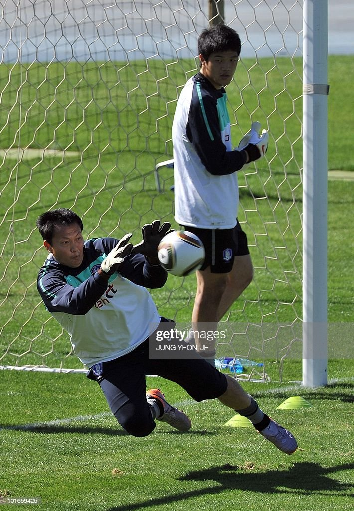South Korean goalkeeper Lee Woon-Jae (bottom) tries to catch the ball as goalkeeper Jung Sung-Ryong (top) looks on during a training session at Olympia Park Stadium in Rustenburg on June 6, 2010 ahead of the start of the 2010 World Cup football tournament.
