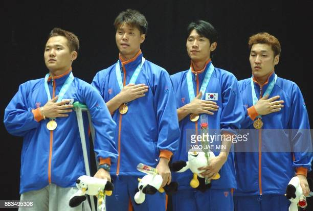South Korean gold medalist fencing team from left Kim Doo Hong Seo Sung Jun Lee Seung Won and Lee Hyuk give honor to their flag during medal ceremony...