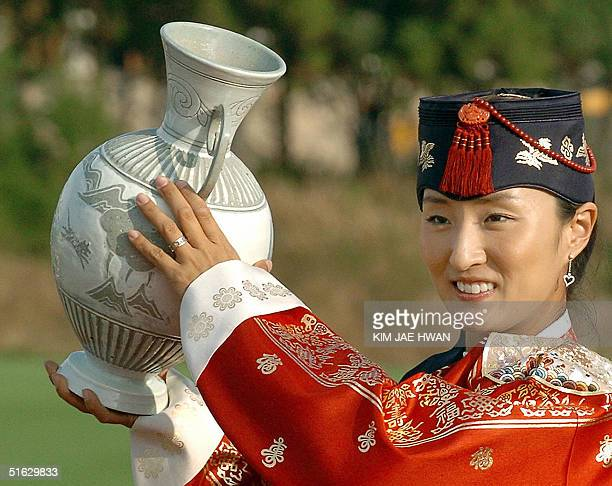 South Korean golfer Grace Park wearing traditional dress holds up the winner's trophy at the awards ceremony after winning the LPGA Nine Bridges...