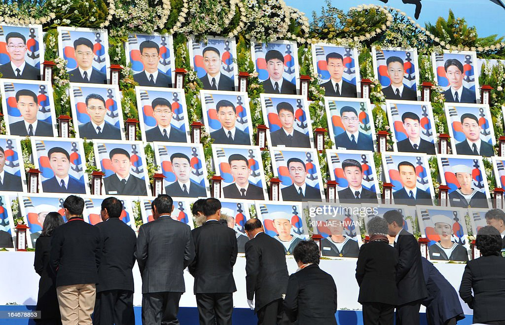 South Korean government officials and civilian delegates pay homage before an altar with pictures of the 46 sailors who died in 2010 when the naval vessel 'Cheonan' was sunk, during a ceremony in the central city of Daejeon on March 26, 2013. Forty-six sailors died after the naval vessel Cheonan was sunk by what Seoul insists was a North Korean submarine. Addressing a ceremony for the 46 sailors, South Korean President Park Geun-Hye warned Pyongyang that its only 'path to survival' lay in abandoning its nuclear and missile programs. AFP PHOTO / POOL/ KIM JAE-HWAN