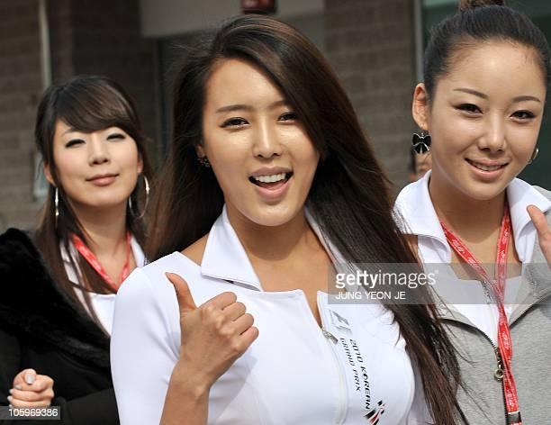 A South Korean grid girl gives the thumbsup as she walks along the paddock at the Korean International Circuit during Formula One's Korean Grand Prix...