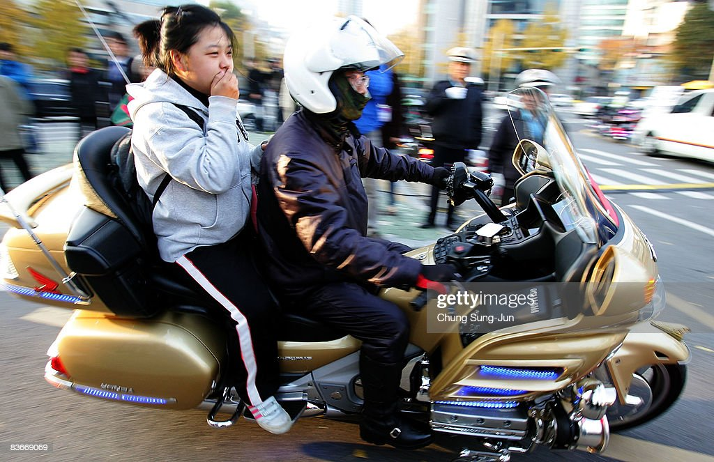 A South Korean high school girl arrives at a school by police bike to take the College Scholastic Ability Test on November 13, 2008 in Seoul, South Korea. More than 580,000 high school seniors and graduates sit for the examinations at 996 test centers across the country. Success in the exam enables students to study at Korea's top universities.