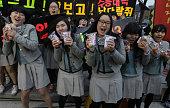 South Korean high school girls cheer for their senior classmates taking the College Scholastic Ability Test on November 8 2012 in Seoul South Korea...
