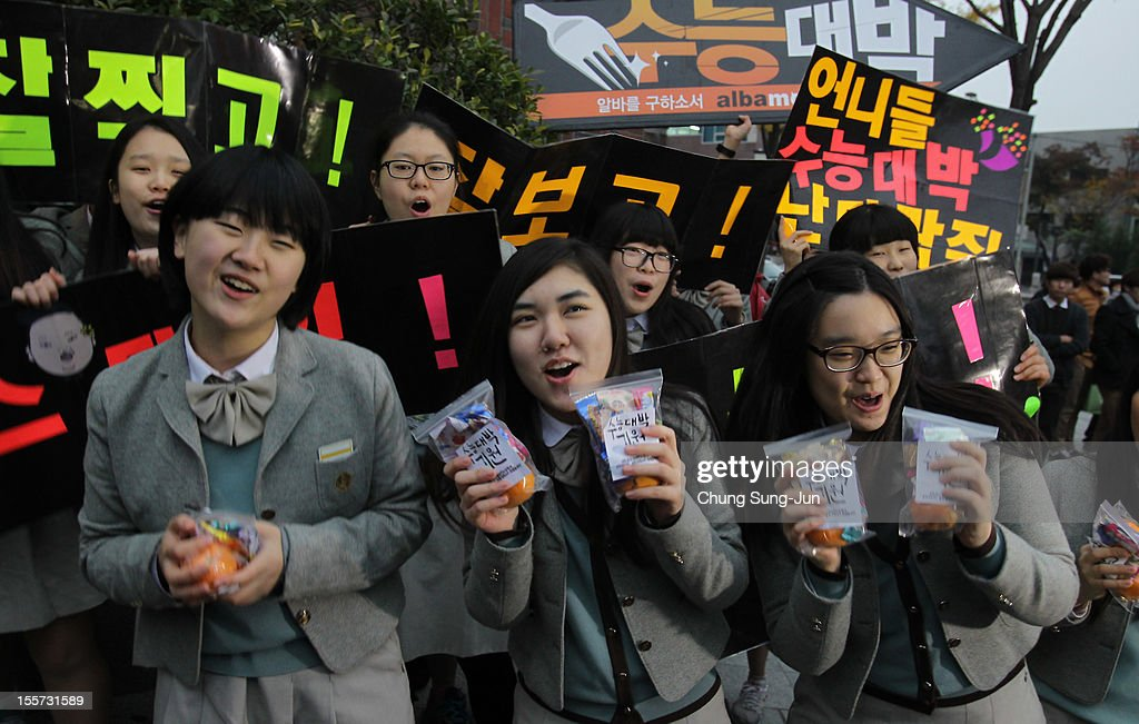 South Korean high school girls cheer for their senior classmates taking the College Scholastic Ability Test on November 8, 2012 in Seoul, South Korea. More than 660,000 high school seniors and graduates sit for the examinations at 1,100 test centers across the country, where academic records are all important. Success in the exam, one of the most rigourous standardized tests in the world, enables students to study at Korea's top universities.