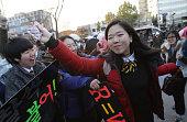 South Korean high school girls cheer for their senior classmates taking the College Scholastic Ability Test on November 13 2014 in Seoul South Korea...