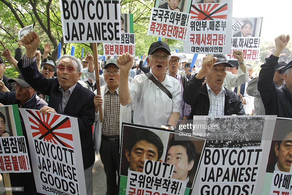 South Korean hold placards carrying the images of Japanese Prime Minister Shinzo Abe and Osaka Mayor Toru Hashimoto during a rally on May 23, 2013 in Seoul, South Korea. Recent remarks by the mayor of Osaka on the historic perception of 'comfort women', conscripted by Japanese military brothels during World War II, have recieved intense criticism from neigbouring countries and the US.