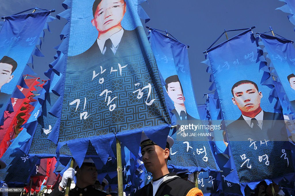 South Korean honour guards hold banners with pictures of some of the 46 sailors who died in 2010 when the naval vessel 'Cheonan' was sunk, during a ceremony in the central city of Daejeon on March 26, 2013. Forty-six sailors died after the naval vessel Cheonan was sunk by what Seoul insists was a North Korean submarine. Addressing a ceremony for the 46 sailors, South Korean President Park Geun-Hye warned Pyongyang that its only 'path to survival' lay in abandoning its nuclear and missile programs. AFP PHOTO / POOL/ KIM JAE-HWAN